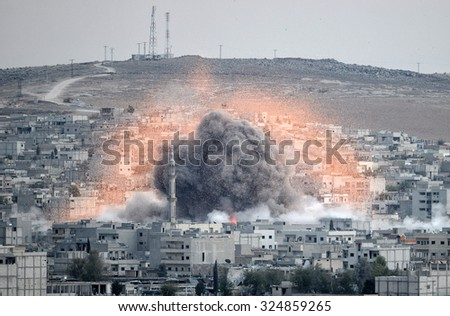 An explosion after an apparent US-led coalition airstrike on Kobane, Syria, as seen from the Turkish side of the border, near Suruc district, 18 October 2014, Turkey , Syria. - stock photo