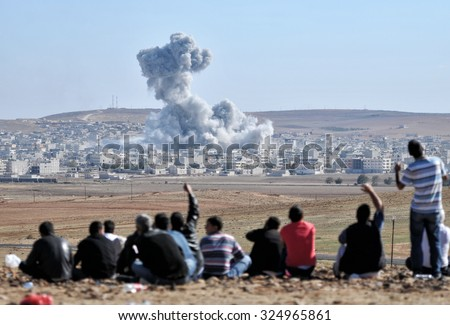 An explosion after an apparent US-led coalition airstrike on Kobane, Syria, as seen from the Turkish side of the border, near Suruc district, 25  October 2014, Sanliurfa, Turkey  - stock photo