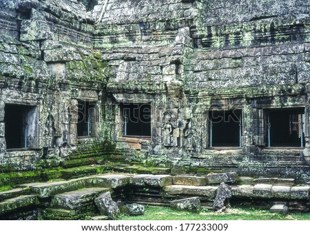 An exterior view of a gallery on the outside of the Ta Prohm Temple in the Angkor Wat area near Siem Reap, Cambodia. The stone walls show the lichen and mos that has grown over the jungle temple. - stock photo