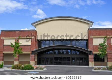 An exterior view of a generic shopping center store building outside in the summer. - stock photo