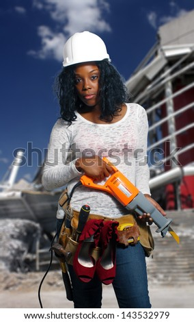 An extraordinarily beautiful young black woman wearing a tool belt that holds her dress shoes, standing in front of a demolished commercial building. - stock photo