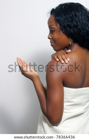 An extraordinarily beautiful young black woman with a captivating smile, wrapped in a bath towel, applies body lotion from a small amount in her hand. - stock photo