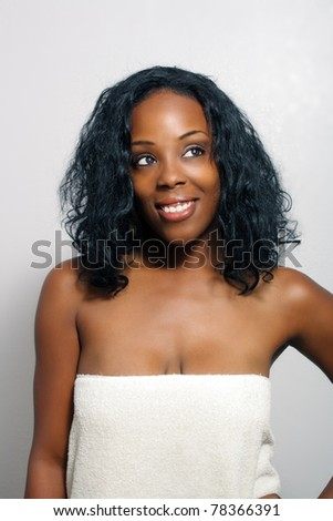 An extraordinarily beautiful young black woman wrapped in a bath towel looks toward frame right. - stock photo