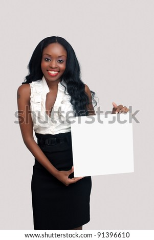 An extraordinarily beautiful young businesswoman holding a blank white card.  Isolated on a light-grey background with generous copyspace.