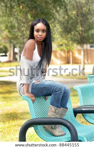An extraordinarily beautiful young woman sits on a park bench.