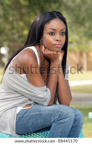 An extraordinarily beautiful young woman sits on a park bench looking off-camera to frame right. - stock photo