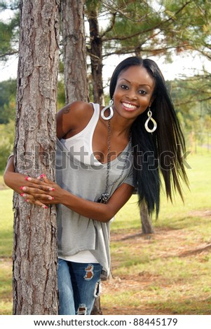 An extraordinarily beautiful young woman with a bright, warm smile leans against a pine tree outdoors. - stock photo