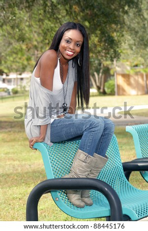 An extraordinarily beautiful young woman with a bright, warm smile sits on a park bench.