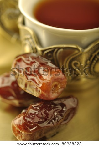 An extreme close up of arabic dates and tea cup - stock photo