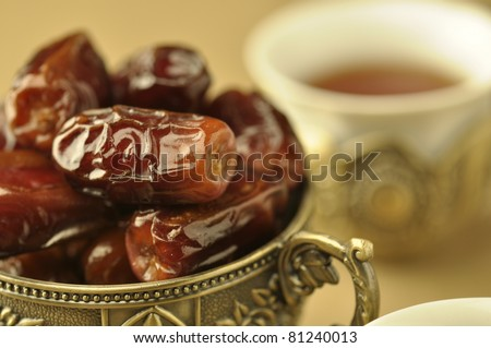 An extreme close up of  golden bowl of dates and tea - stock photo