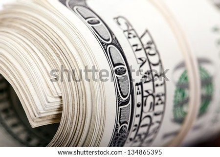 An extreme closeup of a bunch of 100 American Dollars money notes rolled up and held together with a simple rubber band. - stock photo