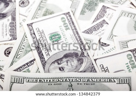 """An extreme macro shot of 100 US$ money notes, depicting the writing """"Untied States of America"""" and the portrait of Benjamin Franklin, amongst the mess of many identical bills. - stock photo"""