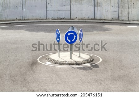 An extremely small roundabout with four identical and absurd traffic signposts of mandatory rotation. - stock photo
