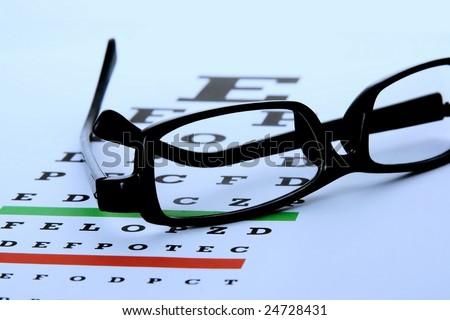 An eye chart with a black frame eyeglasses. - stock photo