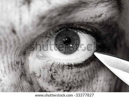 an eye threatened with a knife - stock photo
