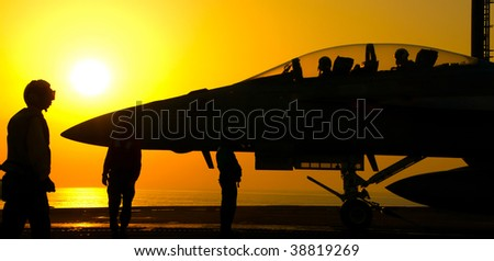 An F-18 Super Hornet readies to launch from an aircraft carrier at sunset
