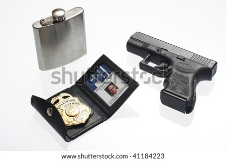 An FBI badge, flask, and pistol on a table.
