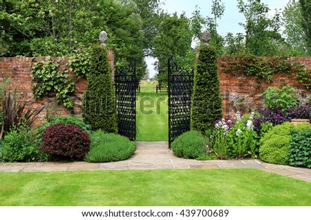 An Formal Landscape garden with wrought iron gates leading to a lawn