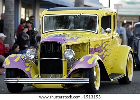 An fully restored classic car cruises the main drag in a car show. - stock photo