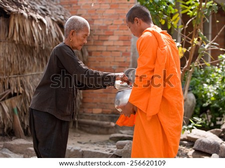 AN GIANG, VIET NAM-FEB 07,2009:  An  Unidentified young monk is receiving morning alms in An Giang province,Southern of Vietnam.  - stock photo