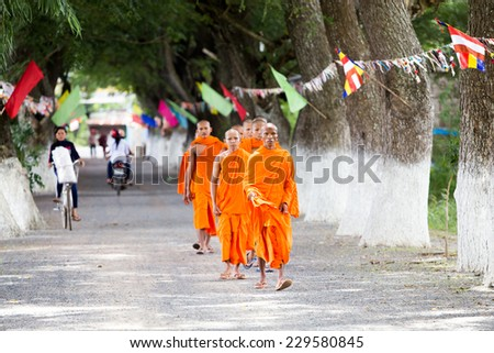 AN GIANG, VIETNAM - Oct 26 2014: Unidentified young monks walking morning alms in An Giang, Vietnam on Oct 26, 2014. Theravada Buddhism arrived from India into the southern Vietnam between 300-600 AD. - stock photo