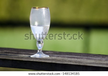 An half empty water cup on wooden fence. - stock photo