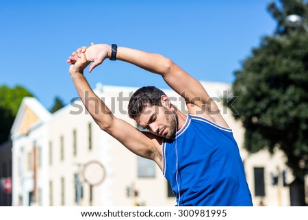 An handsome athlete stretching on a sunny day - stock photo