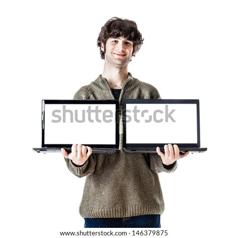 an handsome guy, maybe a student, in casual clothing showing two laptops with blank monitors - stock photo