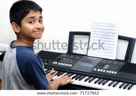 An handsome Indian boy learning music with an electric piano - stock photo
