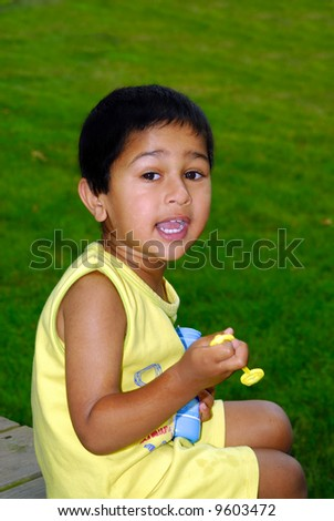 An handsome Indian kid blowing bubbles in the park - stock photo