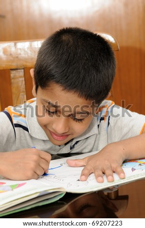 An handsome Indian kid doing his homework very happily - stock photo