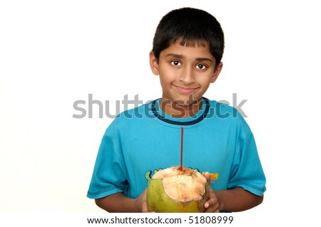 An handsome Indian kid drinking coconut water to cool off - stock photo