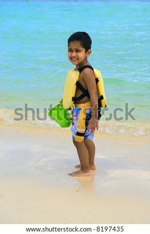 An handsome indian kid having fun at a carrebean beach - stock photo