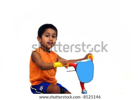 An handsome indian kid having fun in bike - stock photo