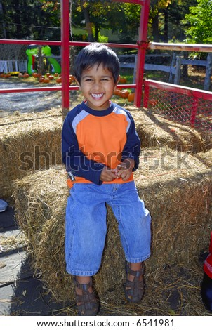 An handsome indian kid having fun with hay ride - stock photo