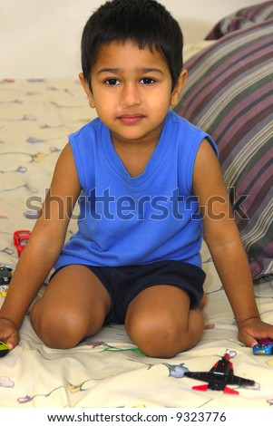 an handsome Indian kid having fun with his toys - stock photo