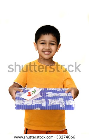 An handsome Indian kid holding a present in his hand