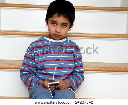 An handsome indian kid listening to music - stock photo