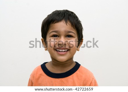 An handsome Indian kid smiling at the camera - stock photo