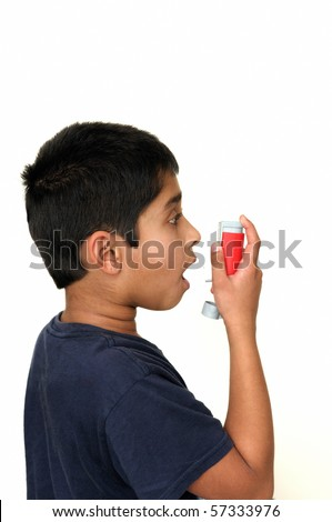 An handsome young Indian child using the inhaler - stock photo