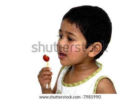 An handsome young Indian kid sucking on a lollypop - stock photo