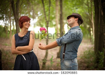 An handsome young man gives a flower to a beautiful girl in the wood, in the warm sun light with a stylish and vintage-like mood.