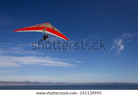 an hang glider flying over Bracciano lake, near Rome, italy in a very clear, sunny day - stock photo
