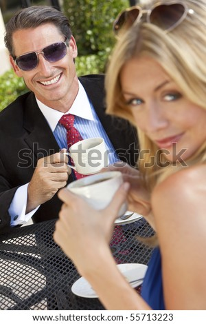 An happy handsome businessman and attractive woman couple having coffee together at an outdoor cafe or restaurant table