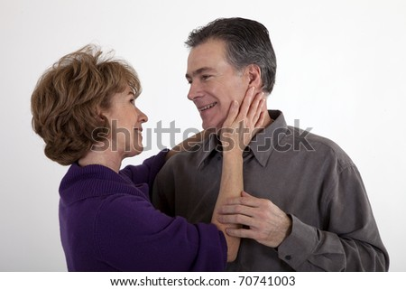 An happy mature couple playfully smile with great affection at each other. - stock photo