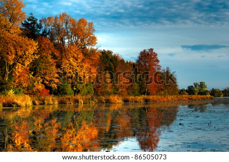 An HDR landscape of a forest in beautiful fall colors reflected in the still waters of a calm river in Ontario, Canada. - stock photo
