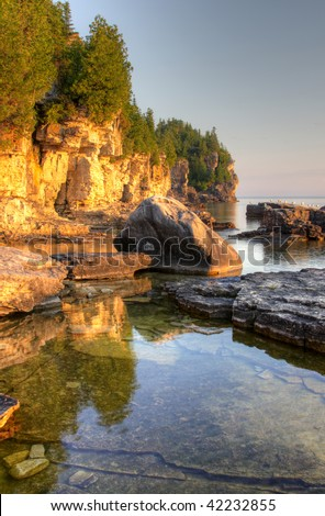 An HDR photo the golden morning light shinning on the rocky shorline of the Bruce Peninsula, in Ontario, Canada. - stock photo