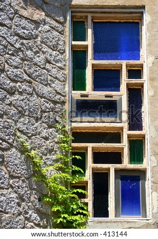 An historically wall with a colorful window on the spanish island Mallorca... - stock photo
