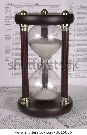 An hour glass rests on tax forms. More tax forms serve as the background. - stock photo