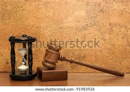 An hourglass and gavel represent a concept based on needing time for legal aid. - stock photo